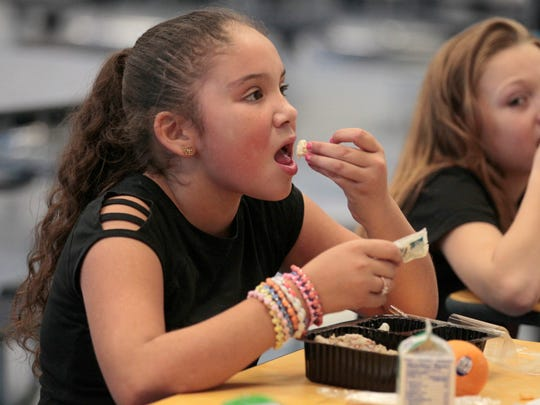 Maniah Tores, 9, of Rochester enjoys a dinner including cauliflower, provided by FoodLink, during the after-school program at School 17 on Orchard Street in Rochester Monday, Oct. 19, 2015.