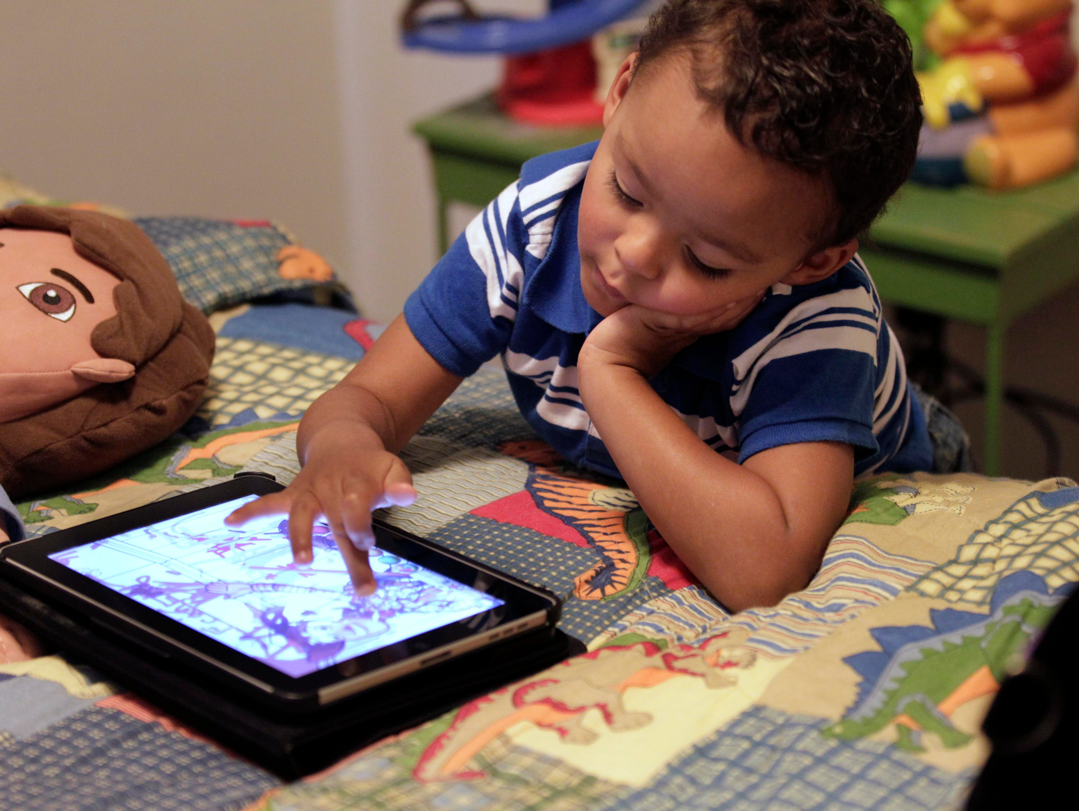 Frankie Thevenot, then 3, plays with an iPad in his bedroom at his home in Metairie, La., in 2011.