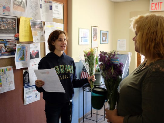Veterans Transition Center staff, flowers in hand, prepare for Friday's Open House event.