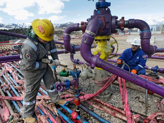 In this March 29, 2013, file photo, workers tend to a well head during a hydraulic fracturing operation outside Rifle in western Colorado.