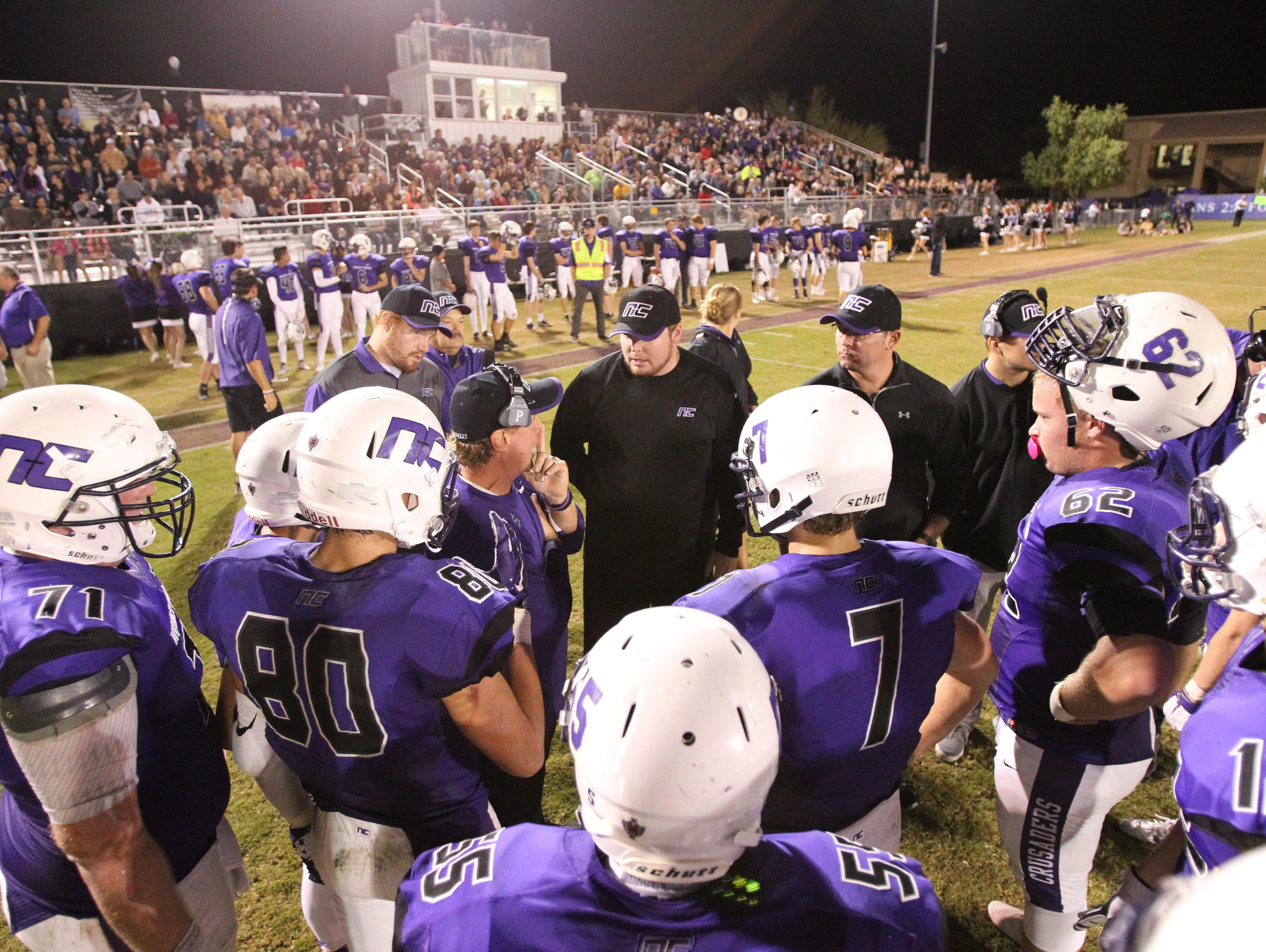 Coach David Inness leads a team timeout in a football game at Northwest Christian School in Phoenix, Arizona on October 30, 2015.