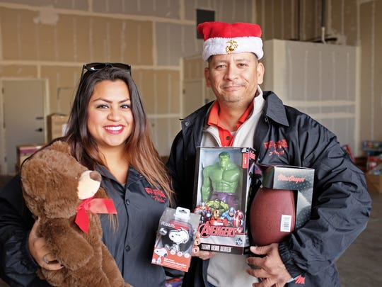 Una Andazola and Larry Sanchez with some of the toys donated to the 2015 Toys for Tots campaign.