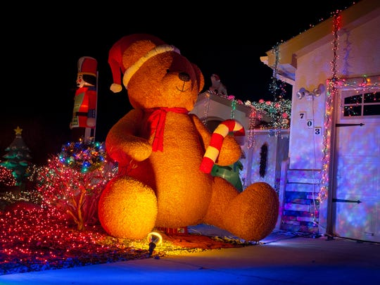 A massive Christmas-themed inflatable teddy bear holds a candy cane in front of Dan Wasser's home.