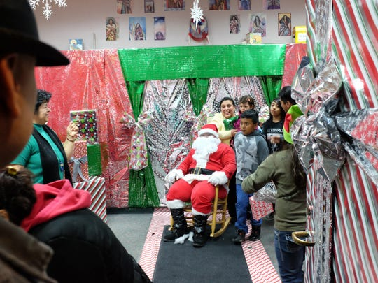Families have their photographs taken with Santa in the library of the Alisal Family Resource Center on Friday.