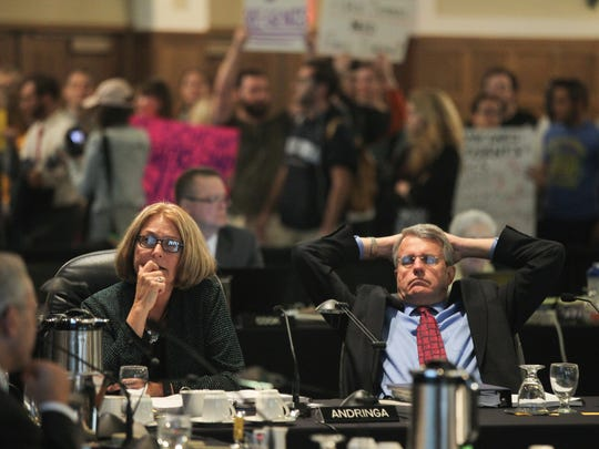 Iowa Regents Mary Andringa and Milt Dakovich continue their meeting as protesters enter the Iowa Memorial Union on Wednesday, Oct. 21, 2015.