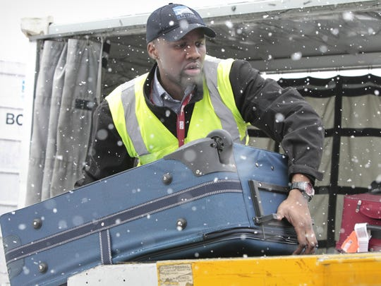 Kyran Ashford unloads luggage from a Southwestern flight at the Greater Rochester International Airport last January. Holiday travel is up at the airport over a year ago.