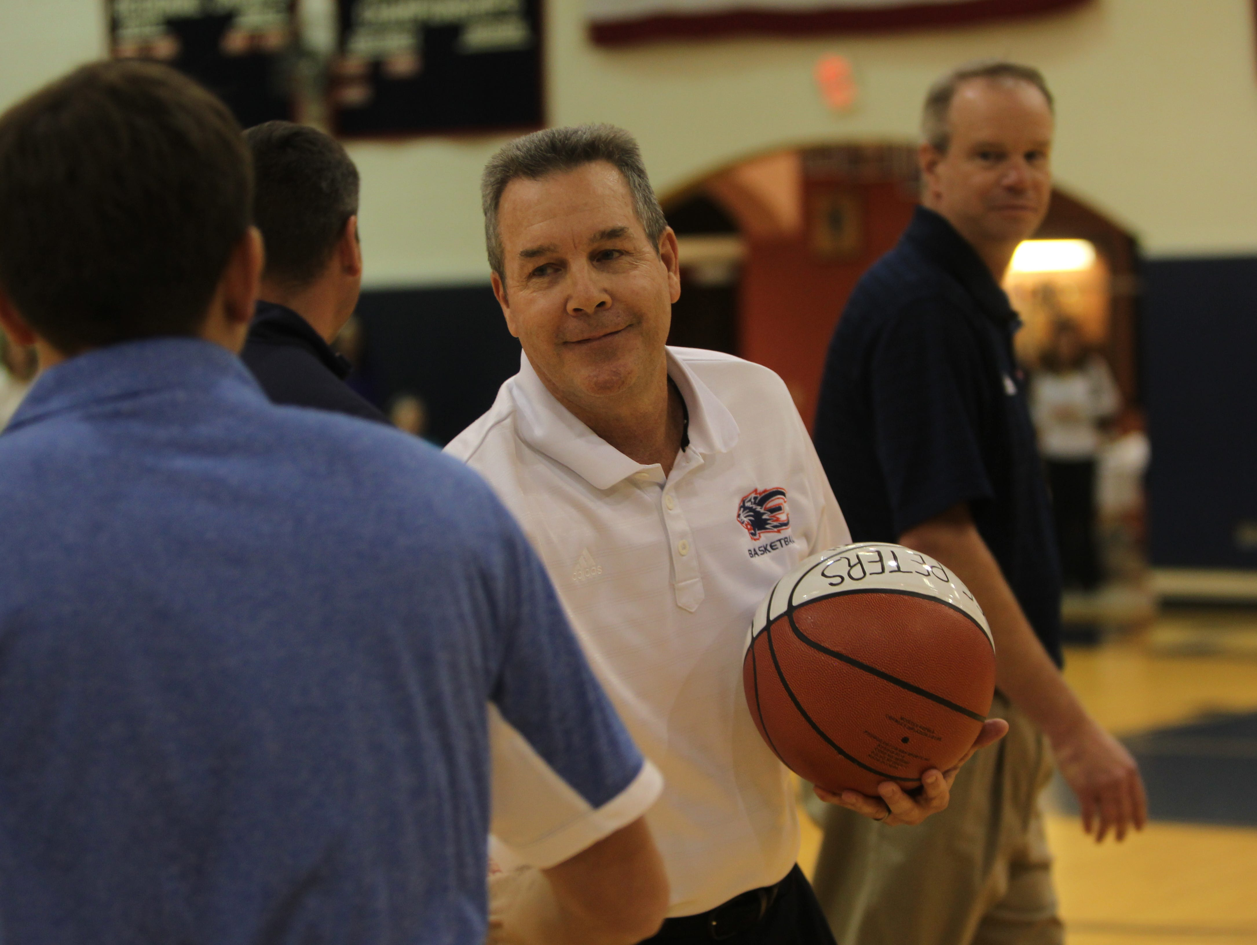 Estero boys basketball coach Lee Peters, center, gets a handshake from Canterbury Coach Darrin Wallace during a ceremony to honor Peters for his 500th career win Wednesday in Estero.