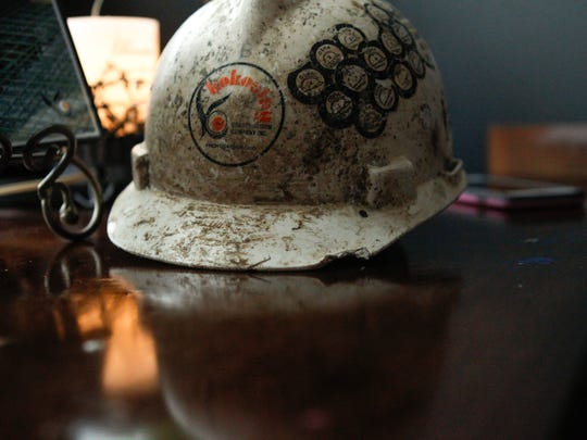 On a side table dedicated to Brandon Carl sits his hard hat next to a photo of him while he worked at Kokosing Construction Co. Kendra Blair, Carl's fiancee, keeps these mementos out to remember Carl after his death in the Hopple Street bridge collapse that occurred one year ago.