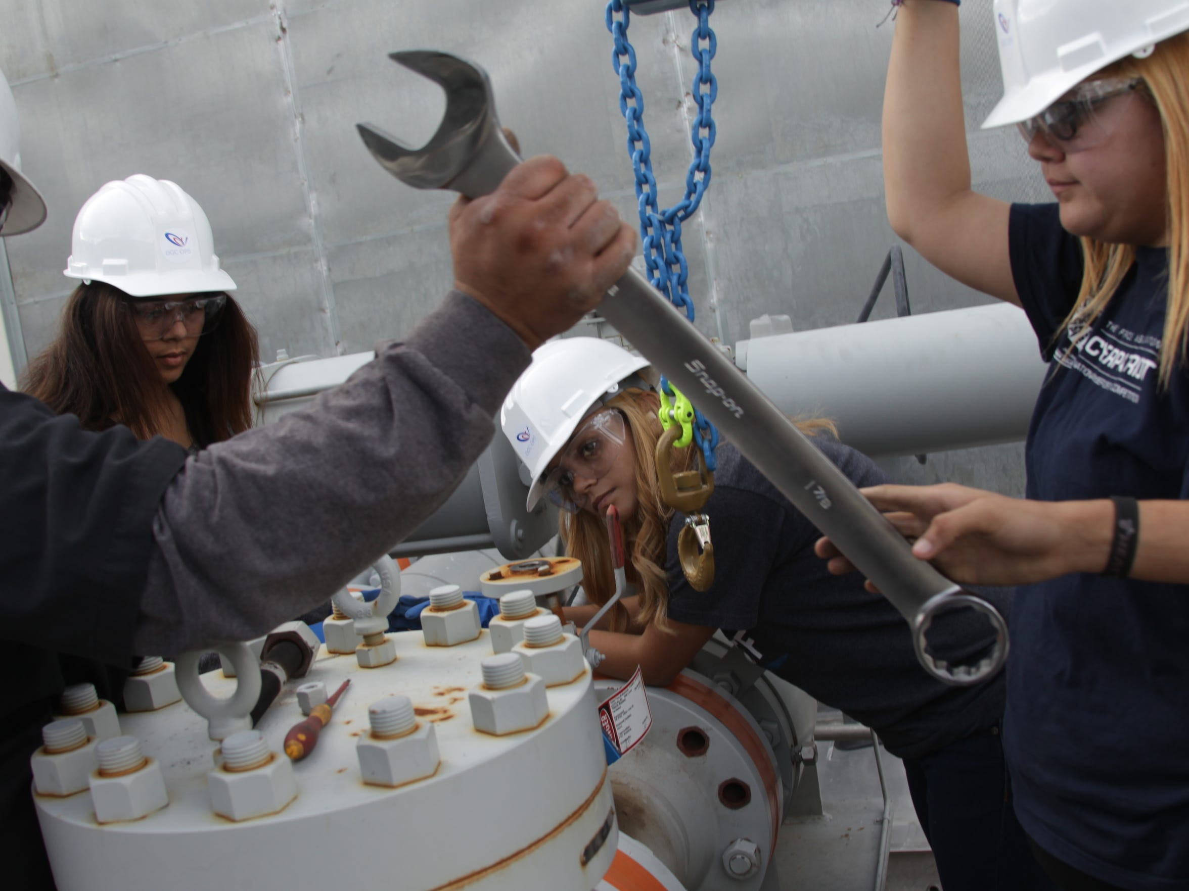 From left to right, Desert Hot Springs High School students Mercedes Henderson, Bricia Romero and Zenaida Chavez help Albert Palalay detach a valve at the CPV Sentinel Energy Project in Desert Hot Springs.