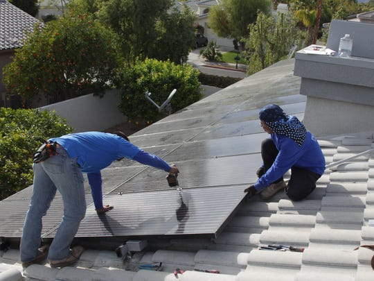 Planet Solar construction manager Ezequiel Alvarez (left) and Juan Arroyo finish installing rooftop panels at a home in Rancho Mirage on Jan. 22, 2016.