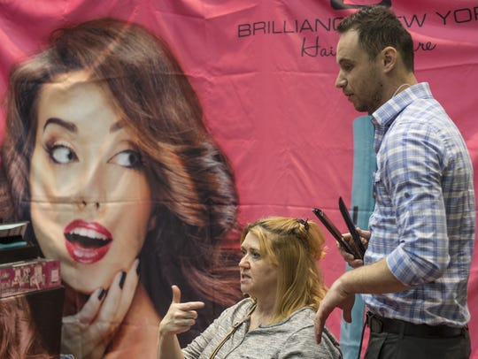 A woman gets her hair curled at the 2015 Mid-Michigan