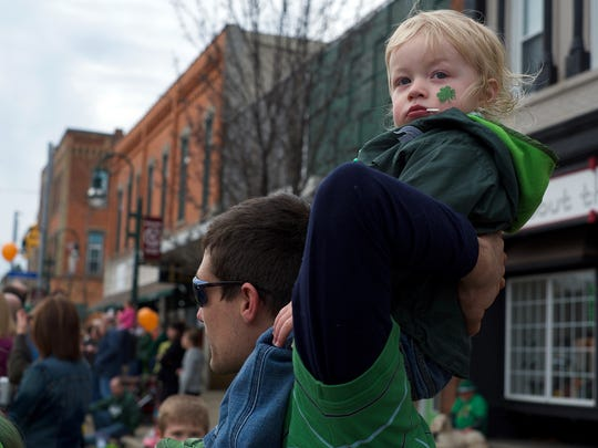 Douglas Fredrickson and his son Douglas Jr. 2, from Grand Ledge watch the annual St. Patrick's Day Parade in Grand Ledge Saturday.