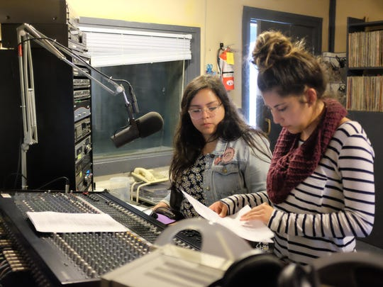 """Producers Felicia Aguilar and Monica Botello consult their scripts before Monday's """"Alza Sun Voz - Speak Out"""" program."""