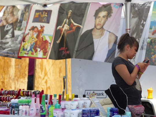 Andrea Amaro, 13, works at the Discoteca Andrea booth on a hot Saturday morning at Glendale 9 Swap Meet.