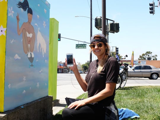 """As she completes one side of """"Cali Girls,"""" artist Gina Roman shows the photo of her friend on a skateboard that inspired it."""