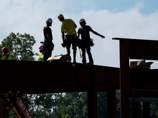 Construction workers on the job at the the Red Cedar Flats student housing project in Meridian Township on Monday, Aug. 29, 2016.