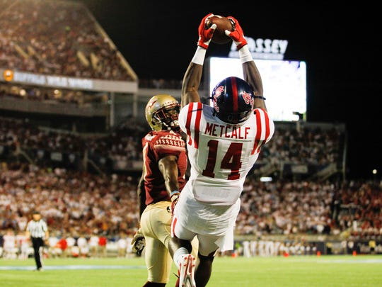 Sep 5, 2016; Orlando, FL, USA; Mississippi Rebels wide receiver D.K. Metcalf (14) catches a touchdown pass as Florida State Seminoles defensive back Tarvarus McFadden (4) defends in the second quarter at Camping World Stadium. Mandatory Credit: Logan Bowles-USA TODAY Sports