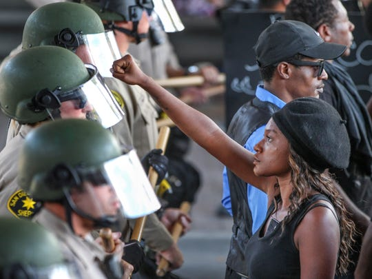 """Ebonay Lee holds up her fist toward a line of  Sheriff's deputies as she and other people protest Wednesday, Sept. 28, 2016, in El Cajon, Calif. Dozens of demonstrators protested the killing of a black man shot by an officer after authorities said the man pulled an object from a pocket, pointed it and assumed a """"shooting stance."""""""