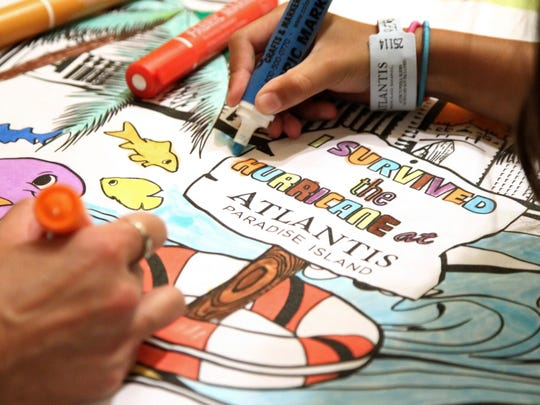 Families pass the time coloring posters provided by their hotel staff while they're kept away from their rooms for safety reasons during the passage of Hurricane Matthew in Nassau, Bahamas, Thursday, Oct. 6, 2016.