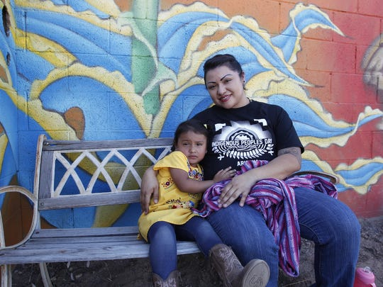 Chef Maria Parra Cano takes a brake from cooking and holds her 3-year-old daughter Yalehua. Parra Cano was preparing beans, squash and deer and bison meat for the Indigenous Peoples Day celebration in Phoenix  on Oct. 10, 2016.