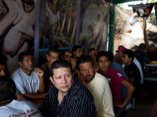 Deportees have lunch at a temporary shelter run by