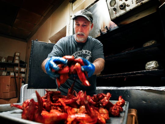 April 16, 2015 - Central BBQ kitchen manager Tom Hastings pulls smoked whole wings from the pit that will be deep fried and tossed in dry rib seasoning before serving to the lunch time crowd.