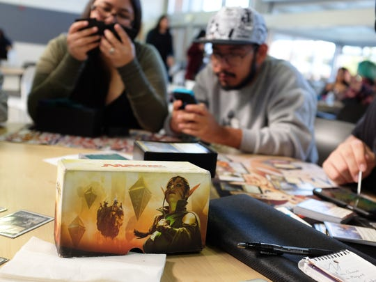 From left, Lisa Walton, Tony Perez and Dakota Sandoval during a game of Magic: The Gathering. Sandoval is simultaneously playing Hearthstone on his mobile phone.
