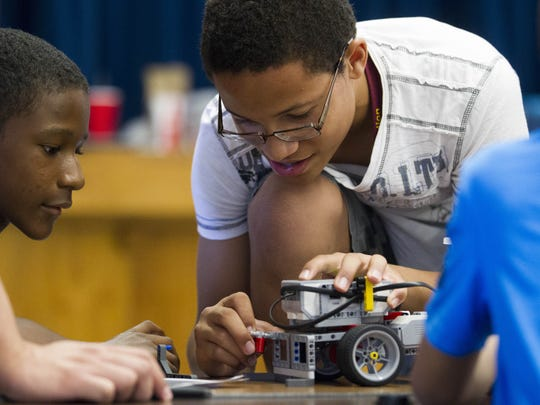 Gerald Bowers (right), 13, tinkers with a robot as