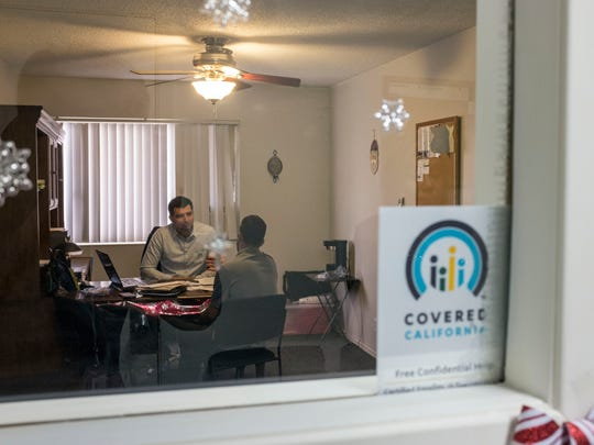 Cesar Perez, an insurance agent specializing in health insurance helps Mohammad Halum, 31, right, signup for Covered California on Thursday, Dec. 15, 2016 at Perez's office in Indio.