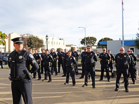 Officers from the Salinas Police Department stand to attention at the City Hall Rotunda before the retirement ceremony of Deputy Chief Daniel Perez on Thursday.