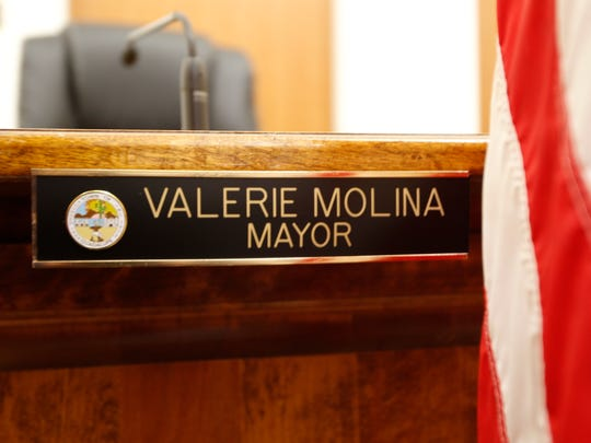 A worker installed the new name plate at the mayor's