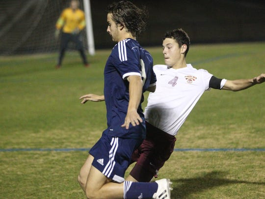 Florida High senior Brandon Kelley slide tackles a ball away from a Maclay attacker during Tuesday's game.