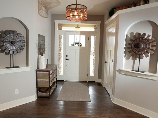 The foyer area includes decorative art niches and windows beside and above the front door.