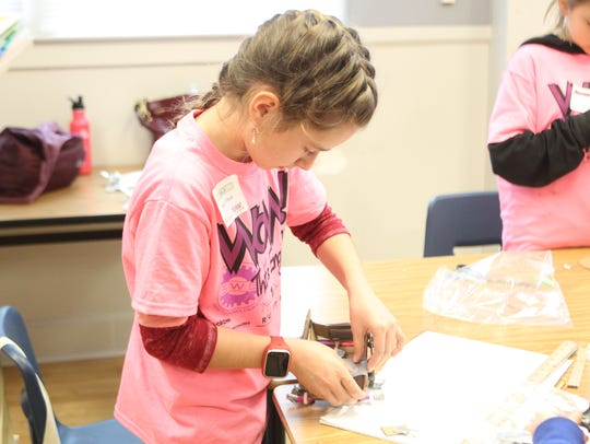Morgan O'Neal, 9, constructs a Mars rover vehicle using