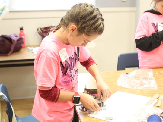 Morgan O'Neal, 9, constructs a Mars rover vehicle using cardboard and rubber bands Saturday at the event hosted by Girls Inc. and the Society of Women Engineers.