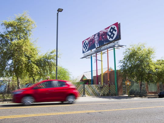 A billboard depicting President Donald Trump flanked