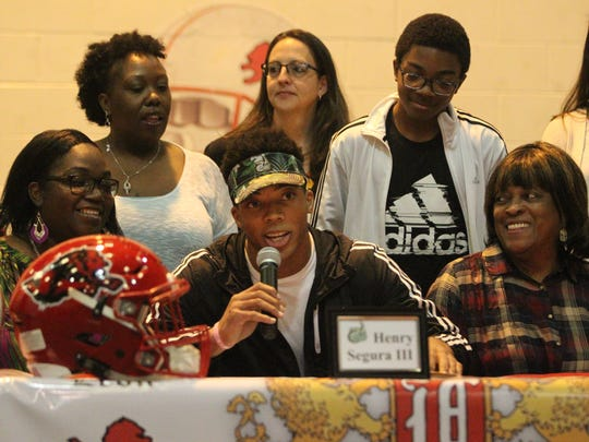 Leon senior Henry Segura III speaks at national signing day with family gathered around prior to signing a football scholarship to Charlotte University.