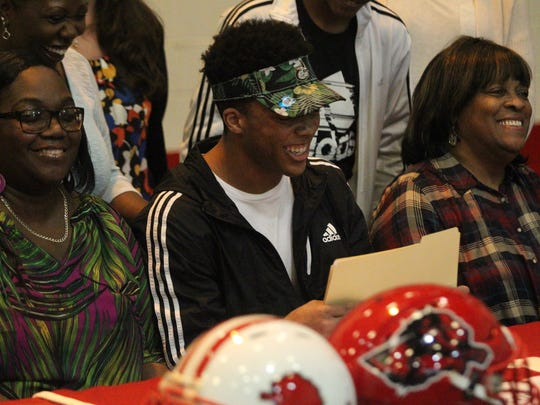 Leon senior Henry Segura III, next to mother Malica (left), signs his letter of intent to play college football at Charlotte University.