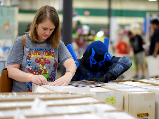 Michele Matthews and her son Cade, 6, who is dressed as Blue Beetle from Young Justice, thumbs through comic books during the 2016 Marble City Comic Con at the Knoxville Expo Center on Saturday, April 23, 2016.