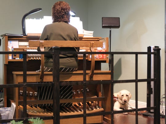 Becky Smith plays the organ at Shasta Baptist Church in Redding. Wilbur finds a nearby spot in the corner.