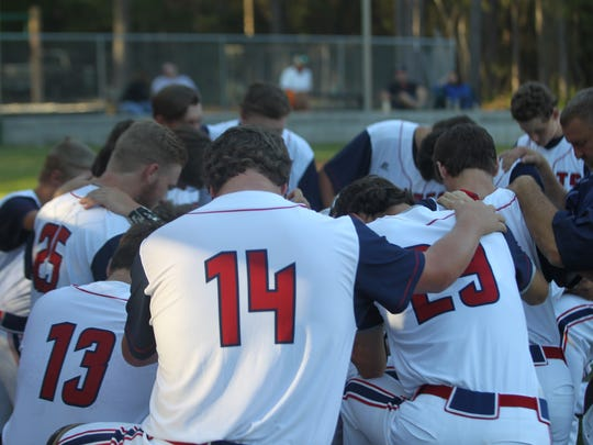 Wakulla Christian's Jaren Lawhon (14) and Peyton Bennet (25) pray with teammates prior to a game.