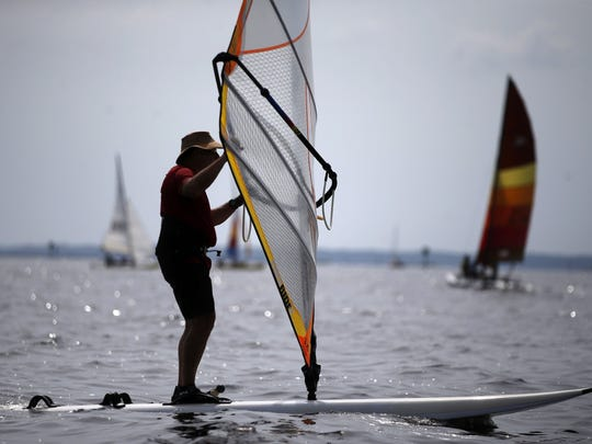 Windsurfers compete during the annual Stephen C. Smith Memorial Regatta at Shell Point Beach. It's important to cover up with suncreen and clothing to protect skin from harmful UV rays.