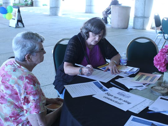 Sharon Smerdon, 59, and her mother, Doris Black, 84, sign up for volunteer activities at CityConnect on Saturday.