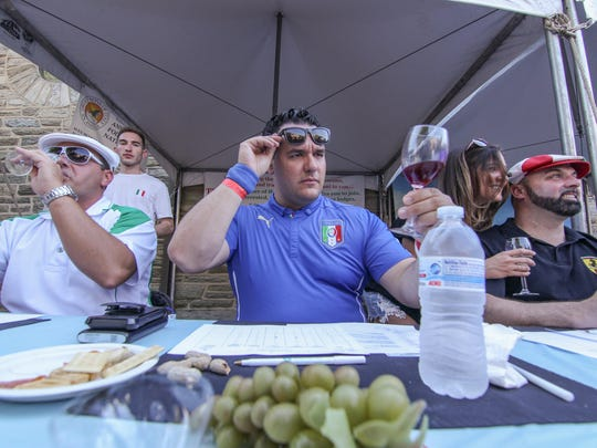 Italo Carrieri-Russo looks at a glass of wine before sipping during a wine tasting on the first day of the annual St. Anthony's Italian Festival on Sunday, June 11, 2017, at St. Anthony's in Wilmington.