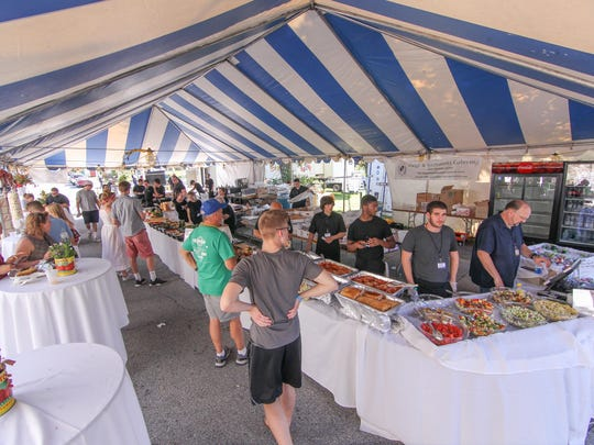 Patrons enjoy food at Luigi & Giovanni tent during the first day of the annual St. Anthony's Italian Festival on Sunday, June 11, 2017, at St. Anthony's in Wilmington.
