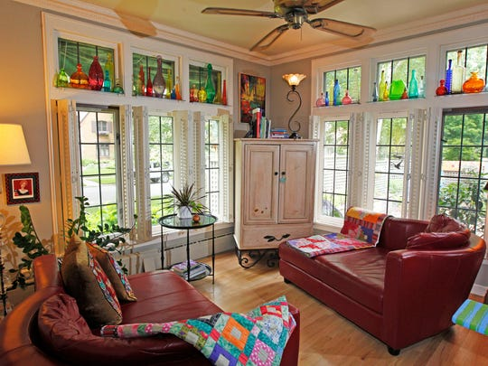 The sunroom with its floor-to-ceiling windows  is one of  Diane Campion favorite rooms in her Whitefish Bay home. Colorful glass bottles reflect light from high-up windows on two sides.