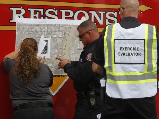 Lafayette Assistant Fire Chief for Special Operations Randy Evans, center, prepares for a mock press briefing during a three-day hazmat drill at the south end of Canal Street.