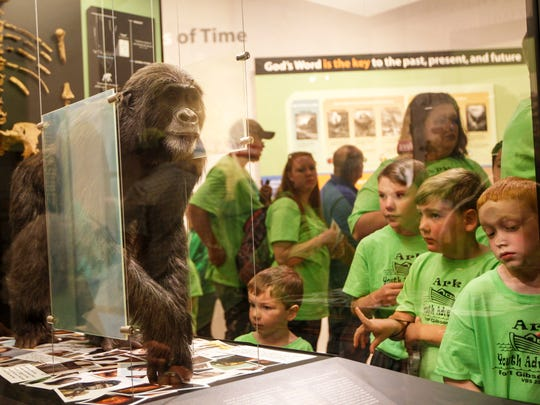 Children look at a lifelike model of Lucy at the Creation