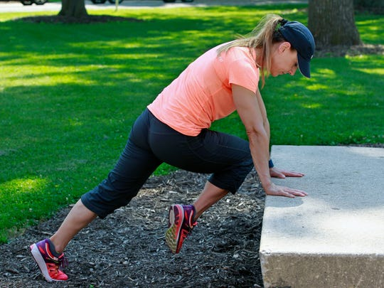 Catherine Andersen,co-owner and personal trainer at Adventure Boot Camp in Milwaukee, demonstrates the criss cross Mt. Climbers from the dorm and campus workout series.