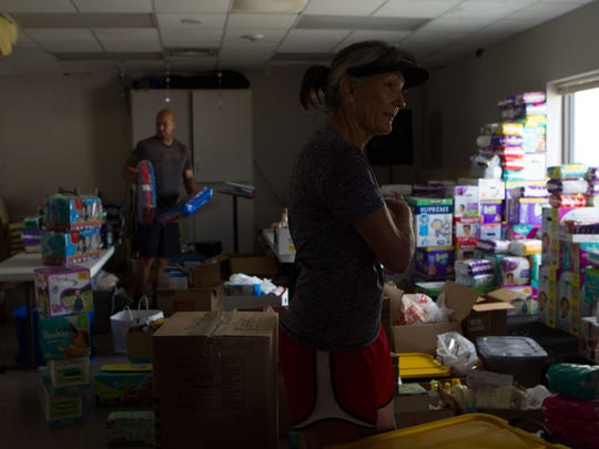 Volunteers Cindy Sallee and Jefferson Maia help sort boxes of donated goods to distribute to members of First Baptist Church in Rockport who need help.